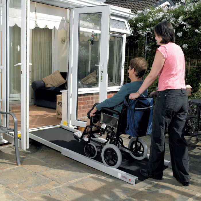 Telescopic aluminium wheelchair ramps used over a door threshold with wheelchair passing over