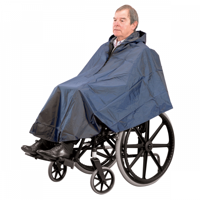A happy man wearing a blue weather resistant wheelchair cape complete with hood